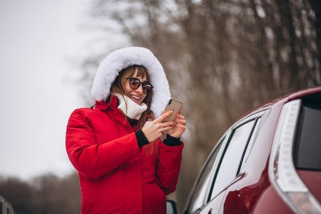Mujer feliz hablando por teléfono afuera en auto en invierno