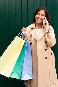 Mujer feliz hablando por teléfono al aire libre mientras sostiene bolsas de la compra.