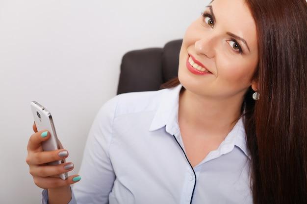 Mujer feliz hablando por teléfono en casa