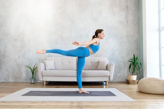 Mujer feliz haciendo deporte en casa haciendo estiramientos de yoga en la habitación