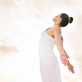 Mujer feliz haciendo yoga bajo el sol