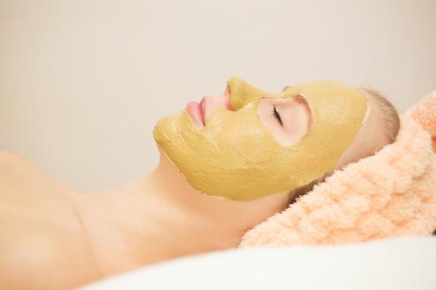 Mujer feliz hermosa en el balneario que hace el tratamiento de la mascarilla. foco selectivo