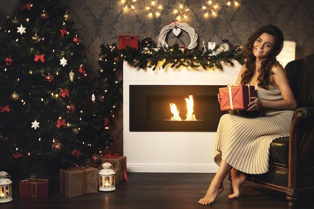 Mujer feliz y hermosa desempacando su regalo de navidad