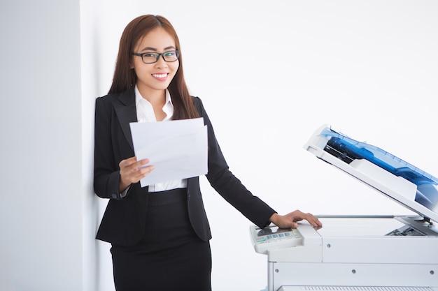 Mujer feliz hermosa de negocios de pie en la copiadora