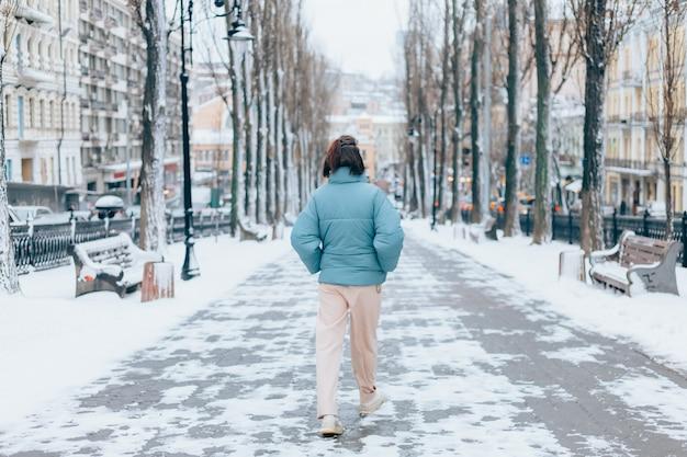 Mujer feliz en invierno en el callejón de la ciudad nevada