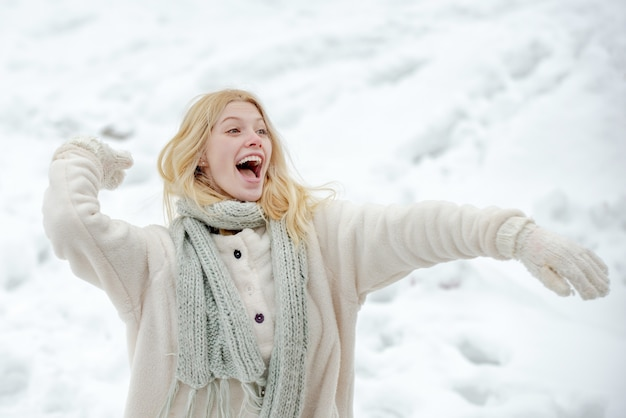 Mujer feliz en invierno mantenga bola de nieve. invierno. bola de nieve y diversión invernal. linda jovencita juguetona al aire libre disfrutando de la primera nieve.