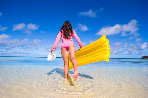 La mujer feliz joven se divierte con el colchón de aire en piscina