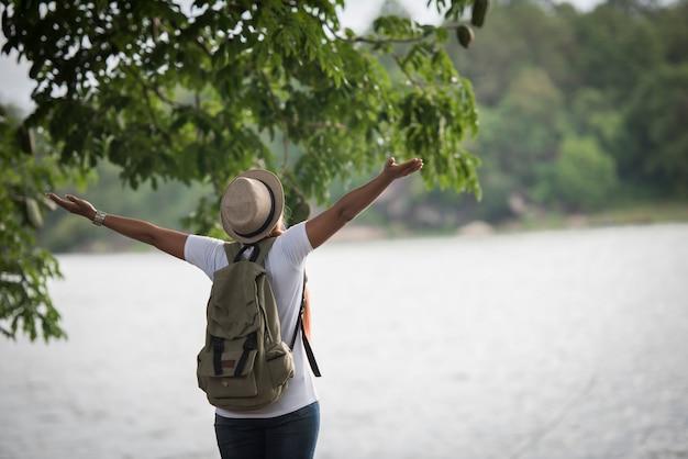 Mujer feliz joven con la mochila que se coloca con las manos aumentadas y que mira al río.