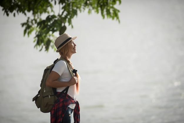 Mujer feliz joven con la mochila que se coloca de mirada al río.