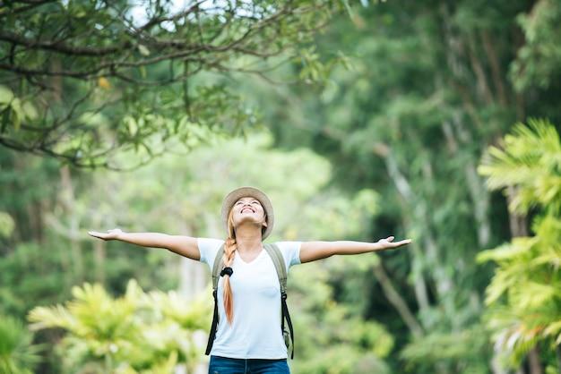 La mujer feliz joven con la mochila que levanta la mano goza con la naturaleza.