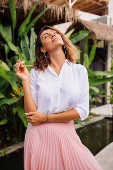 Mujer feliz joven pacífica con el pelo corto y rizado en falda larga rosa y camisa blanca sola fuera de su villa