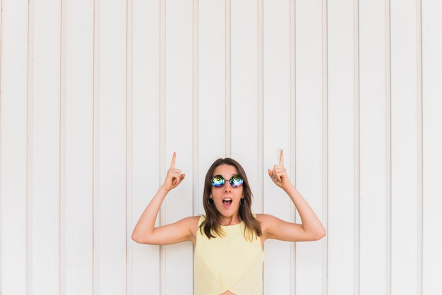 Mujer feliz joven con los pulgares para arriba que presentan en el fondo blanco