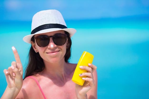Mujer feliz joven que aplica la loción del bronceado en su nariz en la playa blanca