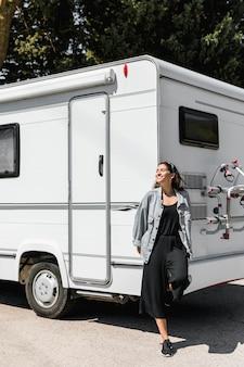 Mujer feliz joven que se inclina en la caravana