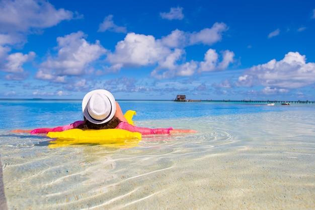 Mujer feliz joven que se relaja con el colchón de aire en piscina