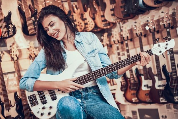 Mujer feliz joven que toca la guitarra eléctrica en tienda musical