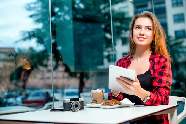 Mujer feliz joven con una tableta que se sienta en café