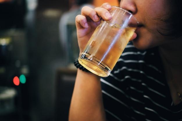 Mujer feliz de los jóvenes que bebe con los cócteles en el restaurante de pub del club nocturno.