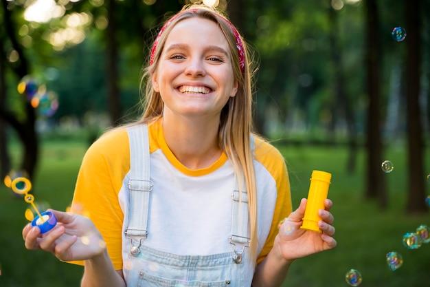 Mujer feliz jugando con burbujas al aire libre