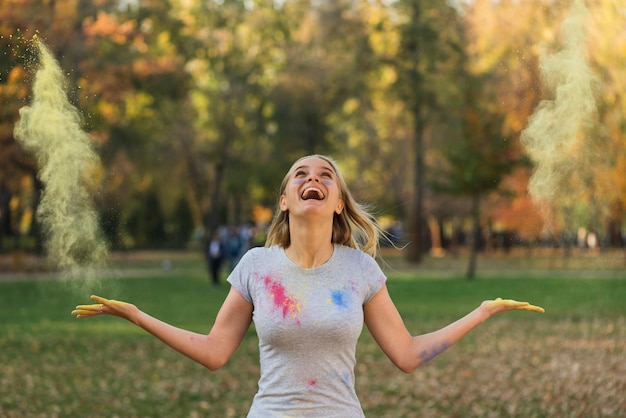 Mujer feliz jugando con color en polvo