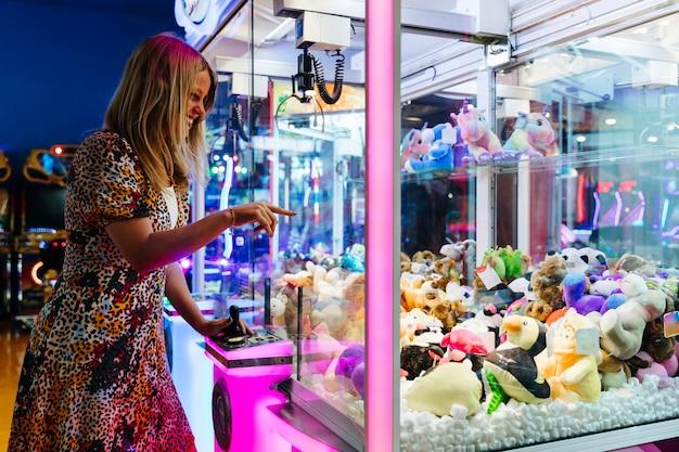 Mujer feliz jugando máquina arcade