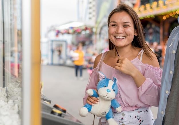Mujer feliz con juguete del juego del parque de atracciones