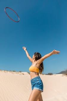 Mujer feliz lanzando hula hoop y caminando sobre la arena