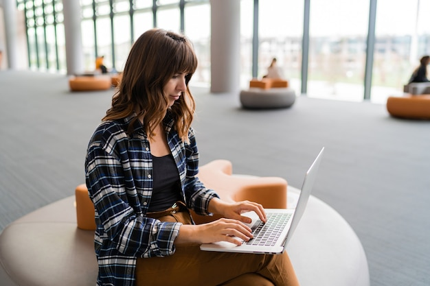 Mujer feliz con lap top mientras está sentado en el salón del aeropuerto.