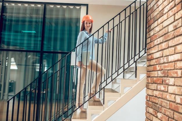 Mujer feliz con laptop en escaleras