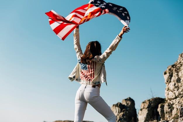 Mujer feliz levantando manos con bandera americana