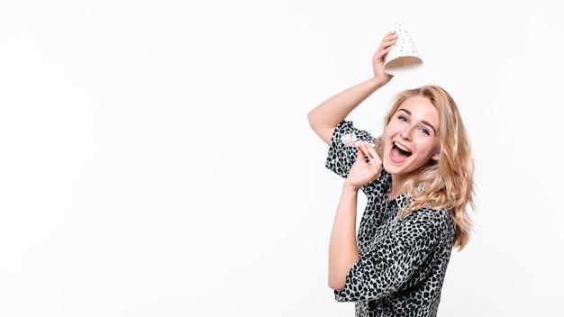 Mujer feliz levantando su sombrero de fiesta