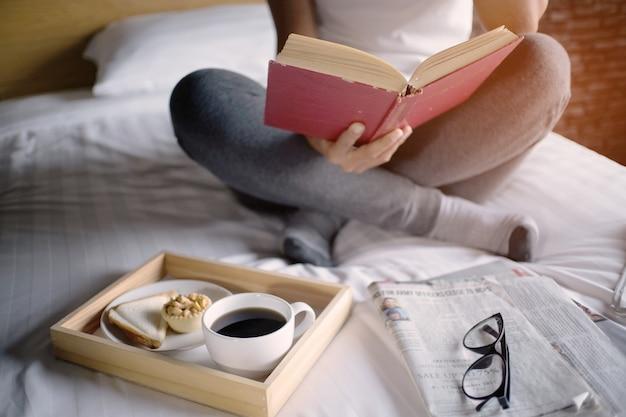 Mujer feliz leyendo un libro y relajándose cómodamente en casa.
