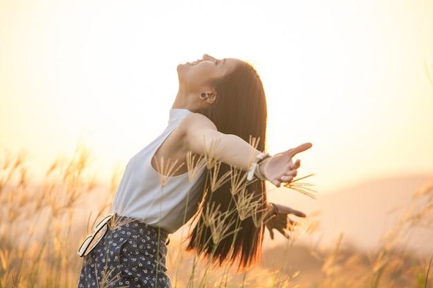 Mujer feliz libre disfrutando del atardecer. hermosa mujer en vestido blanco abrazando el resplandor dorado del sol del atardecer con los brazos extendidos y la cara levantada en el cielo disfrutando de la paz, la serenidad en la naturaleza