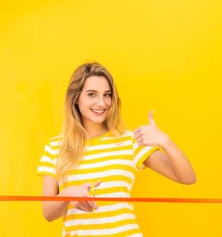 Mujer feliz lista para cortar la cinta roja