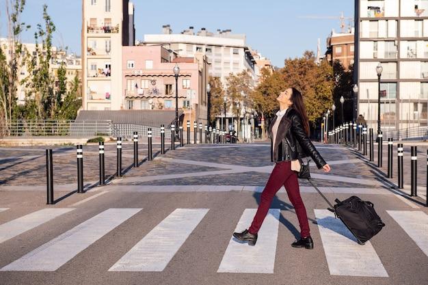 Mujer feliz con maleta cruzando la calle