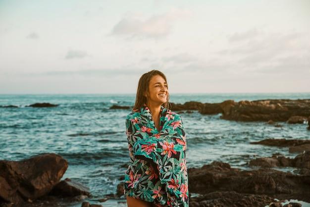 Mujer feliz en manta de pie en la orilla del mar