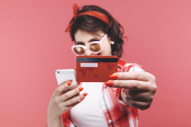 Mujer feliz mantenga tarjeta de crédito. fondo rosa aislado.
