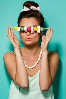 Mujer feliz con maquillaje colorido y dulces dulces en brocheta