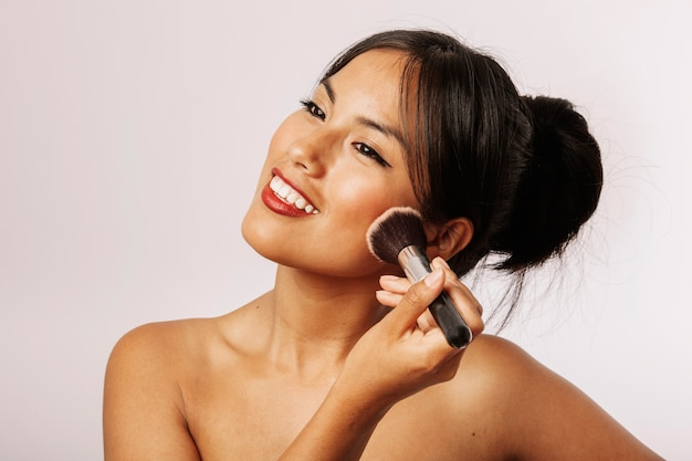Mujer feliz con maquillaje facial
