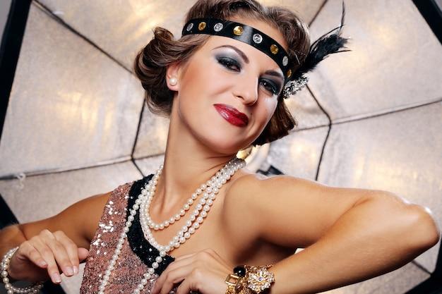Mujer feliz, maquillaje oscuro, perlas