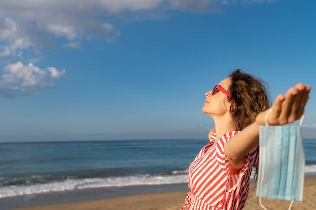 Mujer feliz con máscara médica al aire libre contra el fondo de cielo azul