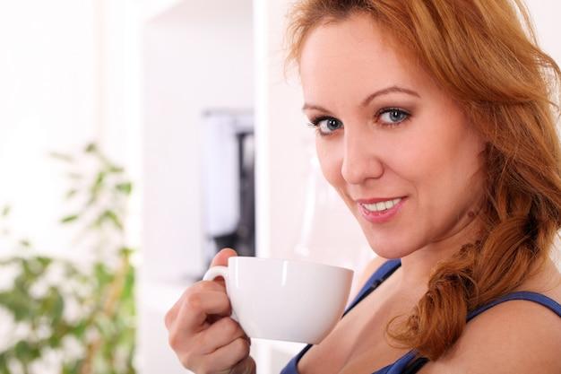 Mujer feliz de mediana edad disfruta de su té