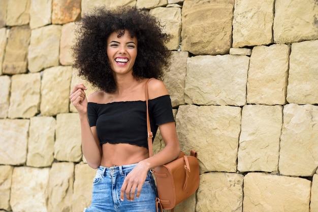 Mujer feliz mezclada con pelo afro riendo al aire libre