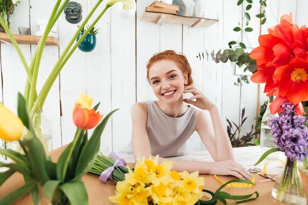 Mujer feliz mientras hace ramos de flores en el taller