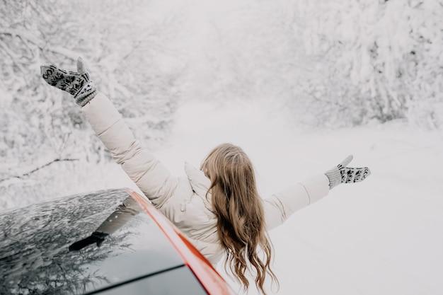 Mujer feliz mira por la ventanilla del coche, extendiendo los brazos en diferentes direcciones. bosque de invierno.