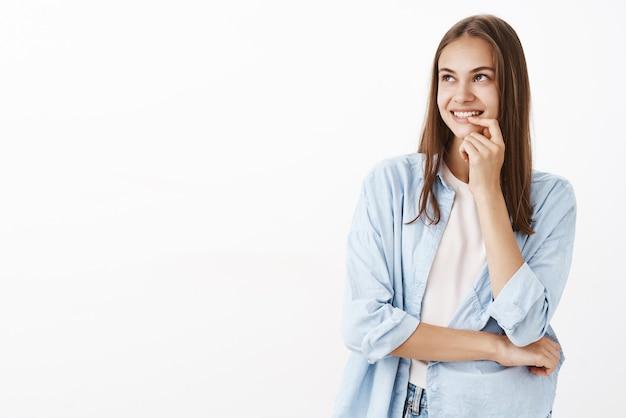 Mujer feliz mirando en la esquina superior izquierda con una sonrisa romántica satisfecha y curiosa sosteniendo el dedo en el labio sonriendo y cruzando el cuerpo con el brazo