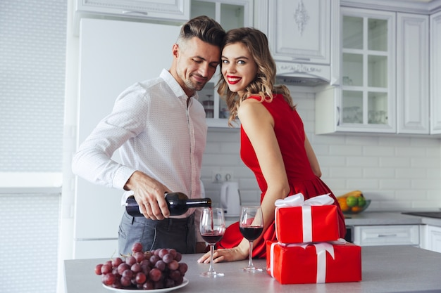 Mujer feliz mirando mientras su hombre vertiendo vino en copas en casa