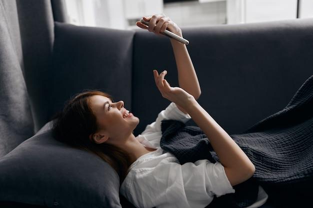 Mujer feliz mirando la pantalla del teléfono mientras está acostado en el sofá en el interior