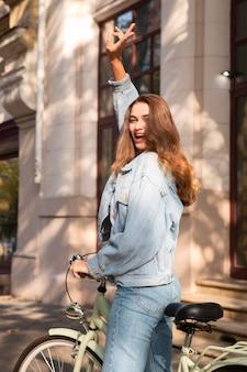 Mujer feliz montando su bicicleta al aire libre en la ciudad