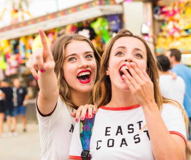 Mujer feliz mostrando algo a su amiga